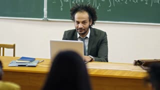 Front view of middle aged university teacher looking at students and using laptop computer when delivering lecture on calculus