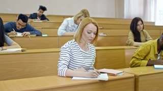 Front view of multi ethnic group of young people sitting in lecture hall and taking notes when studying at university