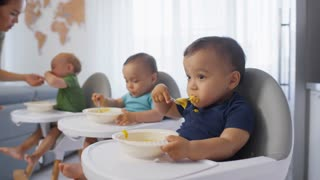 Tracking Shot Of Asian Mother Walking Over And Comforting Crying Toddler Sitting In High Chair In Kitchen While His Twin Siblings Are Busy Eating Baby Puree With Spoons Stock Video Footage