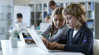 Girl of primary school age helping her classmate with task that they are doing on laptop computer
