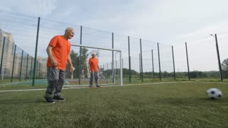 Group of active senior men playing football outdoors in summer, teams dribbling ball and trying to score goal