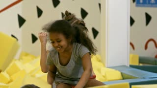 Group of children of different ethnicities playing with yellow soft foam cubes in indoor playground