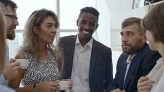 Group of colleagues standing together, talking and laughing over cup of tea during break from work