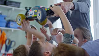 Group of curious multiethnic children of primary school age studying toy car model with male teacher during engineering lesson