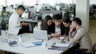 Group of four Asian people sitting at desk in office and discussing project, their female colleague sitting alone and using smartphone