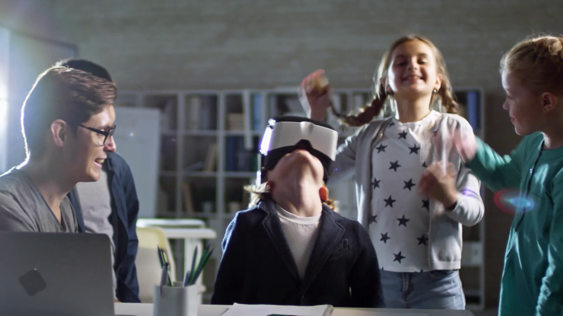 Group of four primary school children, one of them wearing VR glasses, having fun with virtual reality with their teacher at school Stock Video Footage - Storyblocks