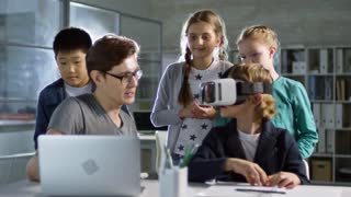 Group of four primary school children, one of them wearing VR glasses, learning to use virtual reality with their teacher