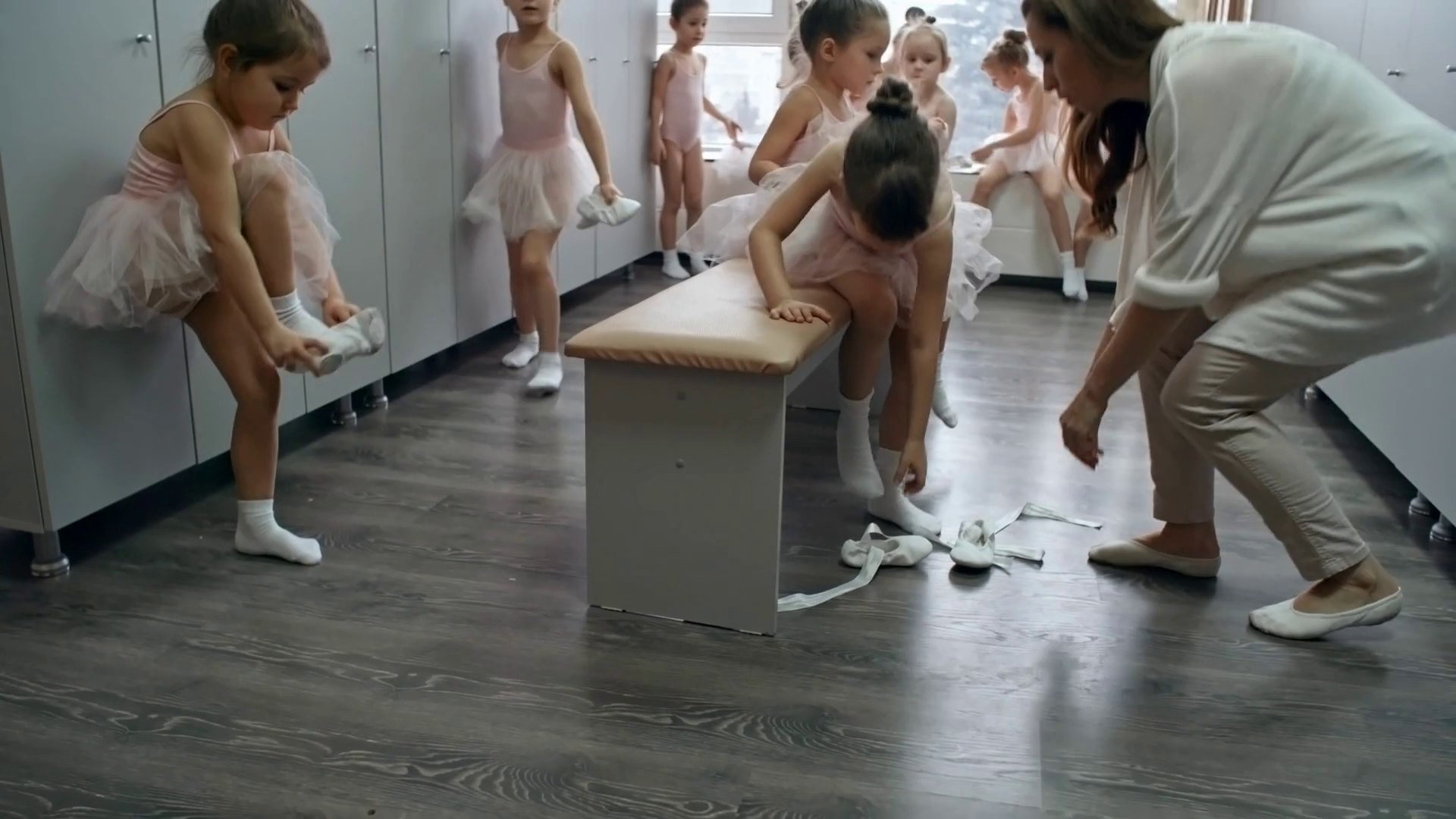 Group of girls of primary school age getting dressed in changing room before having ballet lesson, their teacher helping one of them Stock Video Footage - Storyblocks