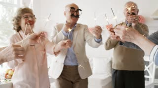 Group of happy senior men and women dancing together in the living room at party: friends holding lightning sparklers and masks on sticks
