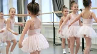 Group of little ballerinas in tutu skirts and leotards practicing ballet moves and spinning in dance class