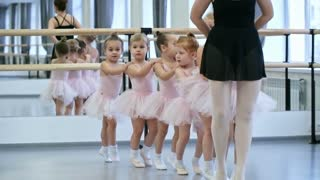 Group of little ballet dancers and their female teacher walking in line when doing warm up exercises for dance class