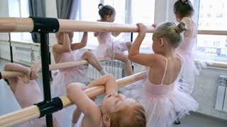 Group of little ballet dancers going crazy at ballet barre when waiting for dance lesson to begin