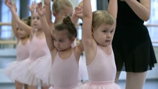 Group of little ballet dancers walking one behind the other and holding hands up in the air, their teacher controlling them, medium shot
