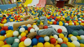 Group of little children of different ethnicities lying in ball pit and smiling when throwing colorful hollow plastic balls