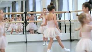 Group of little girls in ballet clothes running around in dance studio before ballet lesson, one of them rehearsing moves
