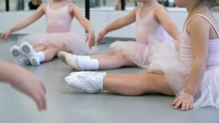 Group of little girls in pink leotards and tutu skirts sitting on the floor with legs stretched and doing warm up exercises in ballet class