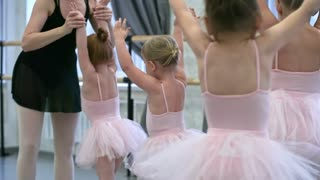 Group of little girls in pink leotards and tutu skirts walking in circle with hands up in the air during warm up in ballet class, their teacher controlling them