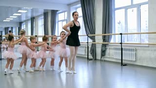 Group of little girls walking on tiptoes one behind the other and repeating new dance movements after their teacher