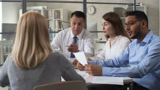 Group of multi-ethnic business professionals discussing ideas at meeting table in the office