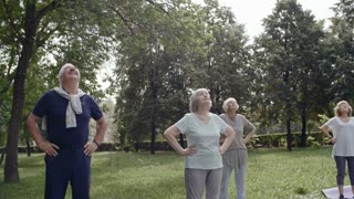 Group of six elderly people and their trainer doing neck warming up exercises and moving their heads up and down during workout in park