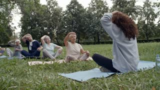 Group of six elderly people sitting in row on yoga mats and following instructions of their young female trainer during workout in park