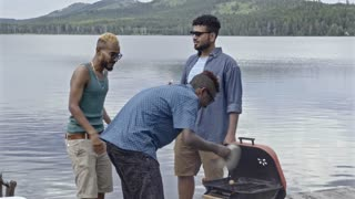 Group of six friends cooking food for picnic by lake, smiling and having fun together, men grilling meat and women standing at table