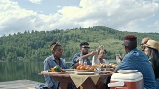 Group of six young people sitting at table during picnic by lake on summer day and clinking bottles