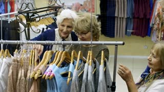 Group of three elderly female friends standing by clothing rack in shopping center, talking to each other and choosing outfits