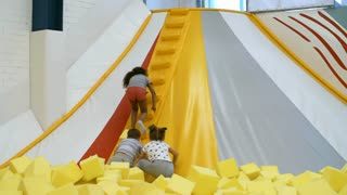 Group of three multi ethnic children climbing stairs of inflatable structure in indoor playground when having fun together