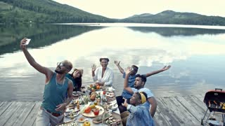 Group of young friends sitting at table, enjoying picnic by lake and posing for smartphone camera