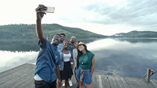 Group of young people standing on wooden dock by lake, smiling and posing for selfie together