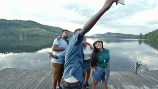 Group of young people standing on wooden dock by lake, waving hands for smartphone camera and posing for selfie