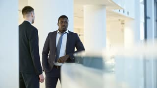 Handheld camera shot of Caucasian and African American office workers standing by glass balustrade in modern business center and talking