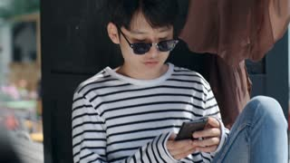 Handheld camera shot of young Asian man in sunglasses sitting on outdoor terrace and typing on smartphone