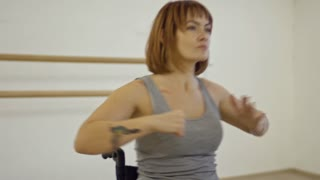 Handheld camera shot of young determined woman sitting in wheelchair and learning dance moves