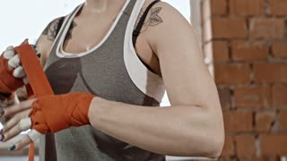 Handheld camera shot of young woman taping her hands with bandage and clenching fists before fight training in gym
