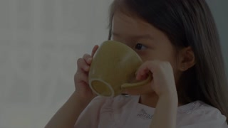 Handheld fade transition shot of cute preschool-age Asian girl drinking milk and eating cookie for breakfast as unrecognizable father wiping her mouth with napkin