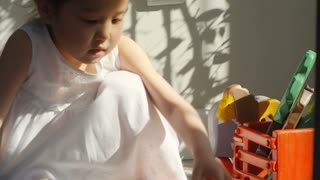 Handheld medium shot of adorable Asian girl playing with wooden toys