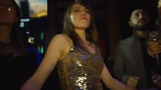 Handheld medium shot of ecstatic multi ethnic young people jumping to rhythmic music and singing karaoke on dance floor