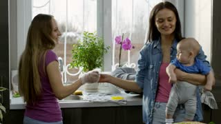Handheld medium shot of happy young woman holding baby boy and giving dirty utensils and wooden boards to female partner washing dishes before sink
