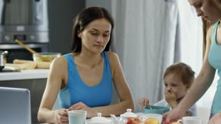 Handheld medium shot of happy young woman sitting at table in morning and talking to female partner pouring hot tea into cups as cute toddler girl eating breakfast