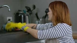 Handheld medium shot of independent woman in wheelchair washing dishes in kitchen