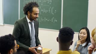 Handheld medium shot of middle-aged teacher of mathematics holding cup of coffee and having friendly conversation with multi ethnic group of students after lecture