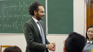 Handheld medium shot of middle eastern man with curly hair explaining equations to multi ethnic group of students after lecture