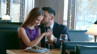 Handheld medium shot of romantic man in suit whispering complements to his beautiful girlfriend on date in restaurant