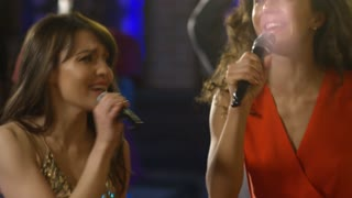 Handheld medium shot of two attractive young women dancing and laughing when singing songs in karaoke bar, group of cheerful multi ethnic people dancing in the background