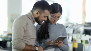 Handheld medium shot of two young Asian people talking to each other and discussing work, woman holding tablet computer and man taking notes in notebook