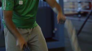Handheld medium shot with slowmo of determined Arab man in sportswear battling ropes in gym