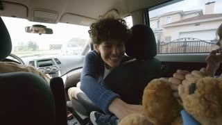 Handheld shot from backseat of moving car: happy mother with short curly hair sitting in passenger seat and giving high-fives to adorable boy with plush toy and cheerful little girl enjoying road trip