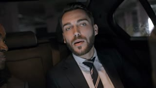 Handheld shot of cheerful bearded businessman in suit chatting with male African colleague while seating on backseat of moving car